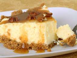 Slice of cheesecake with caramel sauce and pecans